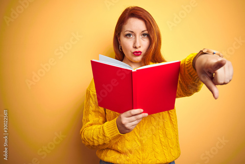 Fotografía  Young redhead teacher woman reading red book over yellow isolated background poi
