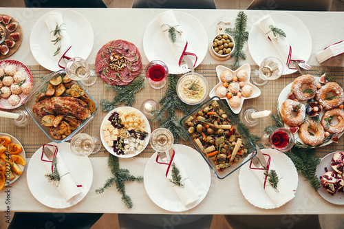 Top view background of beautiful Christmas table with delicious homemade food decorated with fir branches, copy space - 300227447