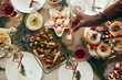 Top view background of hand lighting candle over rustic Christmas table with delicious homemade food decorated with fir branches, copy space