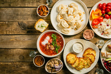 Selection Of Traditional Ukrainian Food - Borsch, Perogies, Potato Cakes, Pickled Vegetables, Top View