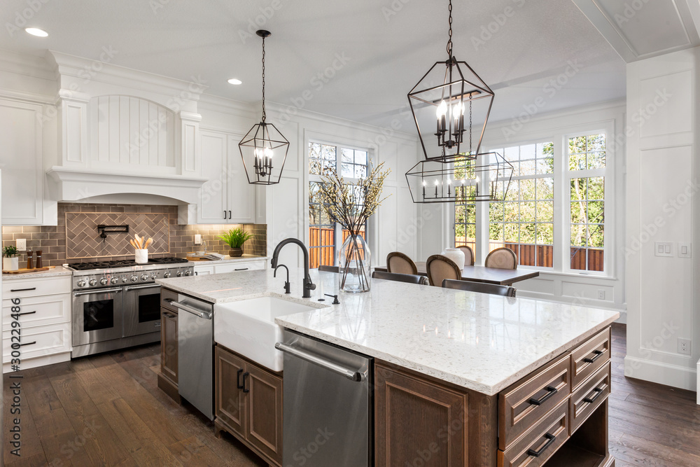 Fototapeta Beautiful kitchen in new traditional style luxury home, with quartz counters, hardwood floors, and stainless steel appliances