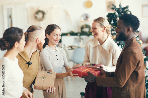 Fotografie, Obraz  Waist up portrait of cheerful young people exchanging presents during Christmas