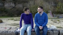 Two Gay Guys From The LGBT Community Sitting On A Stone Pier In A Sweater And Sweatshirt