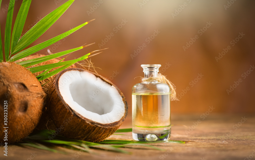 Fototapeta Coconut palm oil in a bottle with coconuts and green palm tree leaf on brown background. Coco nut closeup. Healthy Food, skin care concept. Vegan food. Skincare treatments. Aromatherapy