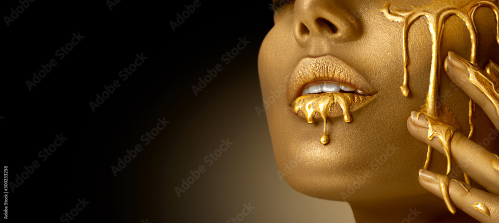 Fototapeta Gold Paint smudges drips from the face lips and hand, lipgloss dripping from sexy lips, golden liquid drops on beautiful model girl's mouth, gold metallic skin make-up. Beauty woman makeup close up