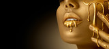 Gold Paint smudges drips from the face lips and hand, lipgloss dripping from sexy lips, golden liquid drops on beautiful model girl's mouth, gold metallic skin make-up. Beauty woman makeup close up