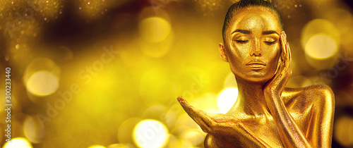 Obrazy nowoczesne   gold-woman-skin-christmas-beauty-fashion-model-girl-with-golden-make-up-hair-and-jewellery-on-gold-background-pointing-hand-proposing-products-sales-metallic-glance-fashion-art-portrait-glamour