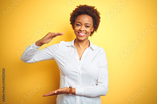 Fototapeta African american business woman over isolated yellow background gesturing with hands showing big and large size sign, measure symbol. Smiling looking at the camera. Measuring concept. obraz