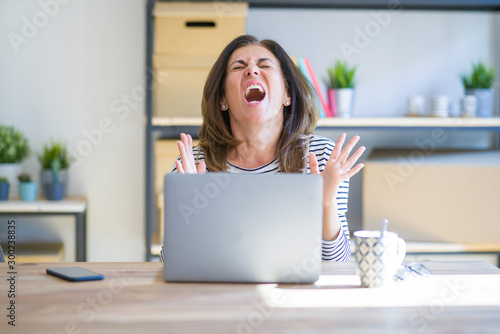 Middle age senior woman sitting at the table at home working using computer laptop crazy and mad shouting and yelling with aggressive expression and arms raised Canvas Print