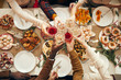 Leinwanddruck Bild - Top view background of people raising glasses over festive dinner table while celebrating Christmas with friends and family, copy space