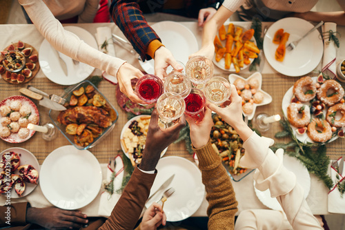 Fototapeta Top view background of people raising glasses over festive dinner table while celebrating Christmas with friends and family, copy space obraz