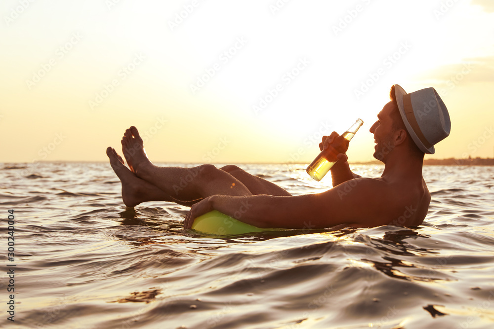 Fototapety, obrazy: Young man with drink on inflatable ring in sea