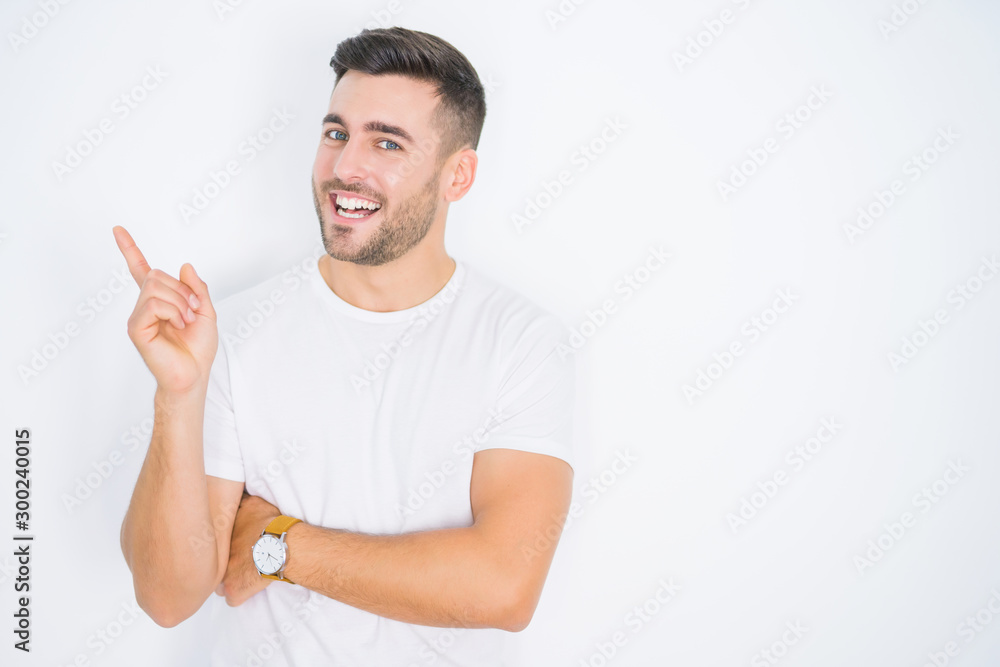 Fototapeta Young handsome man wearing casual white t-shirt over white isolated background with a big smile on face, pointing with hand and finger to the side looking at the camera.