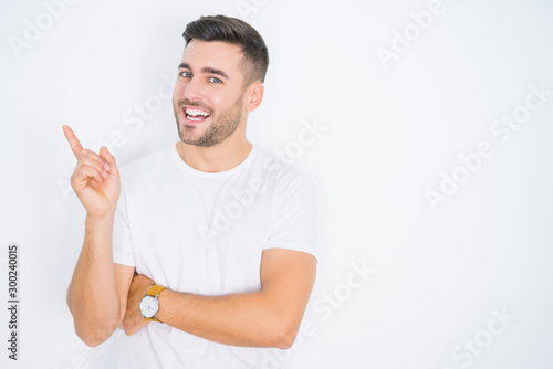 Pinturas sobre lienzo  Young handsome man wearing casual white t-shirt over white isolated background with a big smile on face, pointing with hand and finger to the side looking at the camera