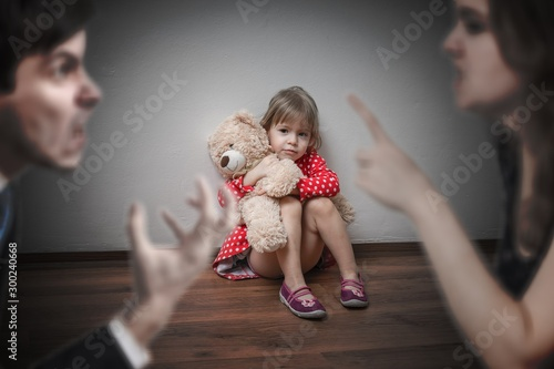 Divorce concept. Sad child is sitting at floor when parents argu Tapéta, Fotótapéta