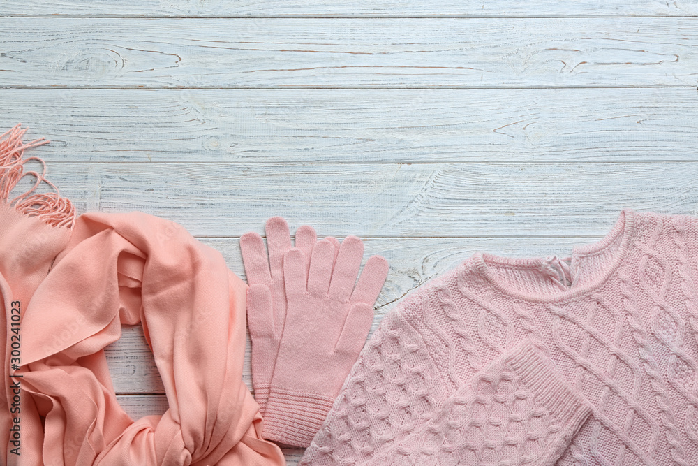 Fototapeta Flat lay composition with warm clothes on white wooden background. Space for text