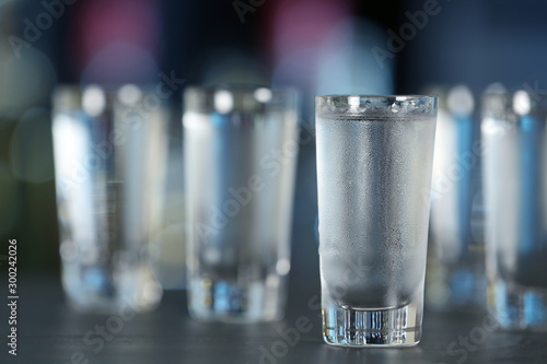 Papiers peints Bar Shot of vodka on table against blurred background. Space for text