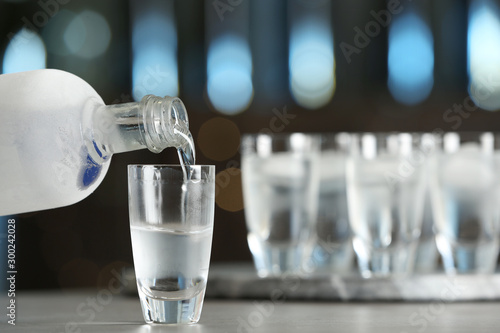 Pouring vodka from bottle into shot glass on bar counter. Space for text - 300242028