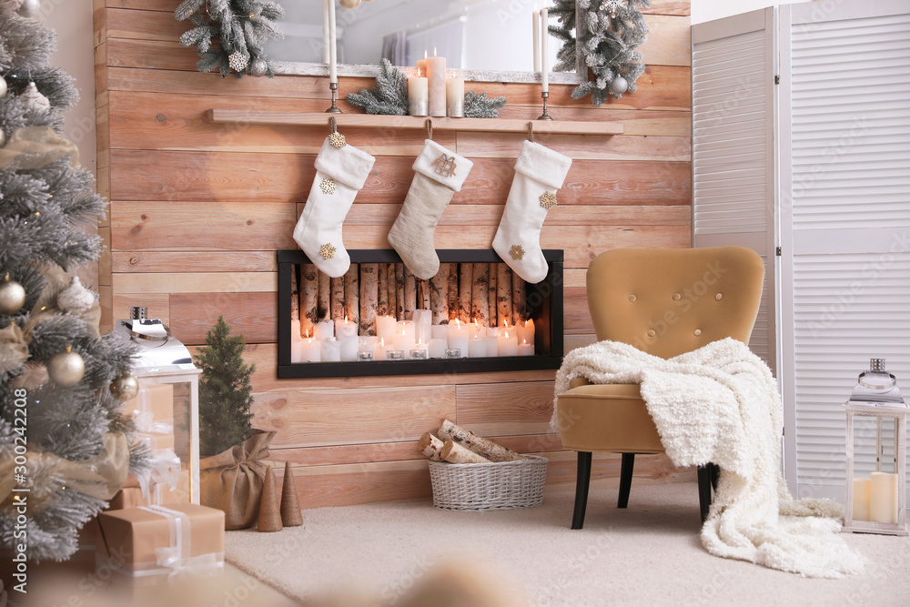 Fototapeta Fireplace with Christmas stockings in room. Festive interior