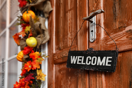 Fotomural  Sign with word WELCOME hanging on door