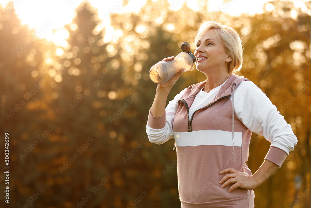 Fototapeta Sporty mature woman with bottle of water outdoors - obraz na płótnie