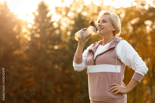 Obraz Sporty mature woman with bottle of water outdoors - fototapety do salonu