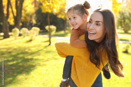 Obraz Happy woman with little daughter in sunny park. Autumn walk - fototapety do salonu