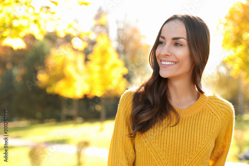 Beautiful woman wearing yellow sweater in park. Autumn walk Fototapet