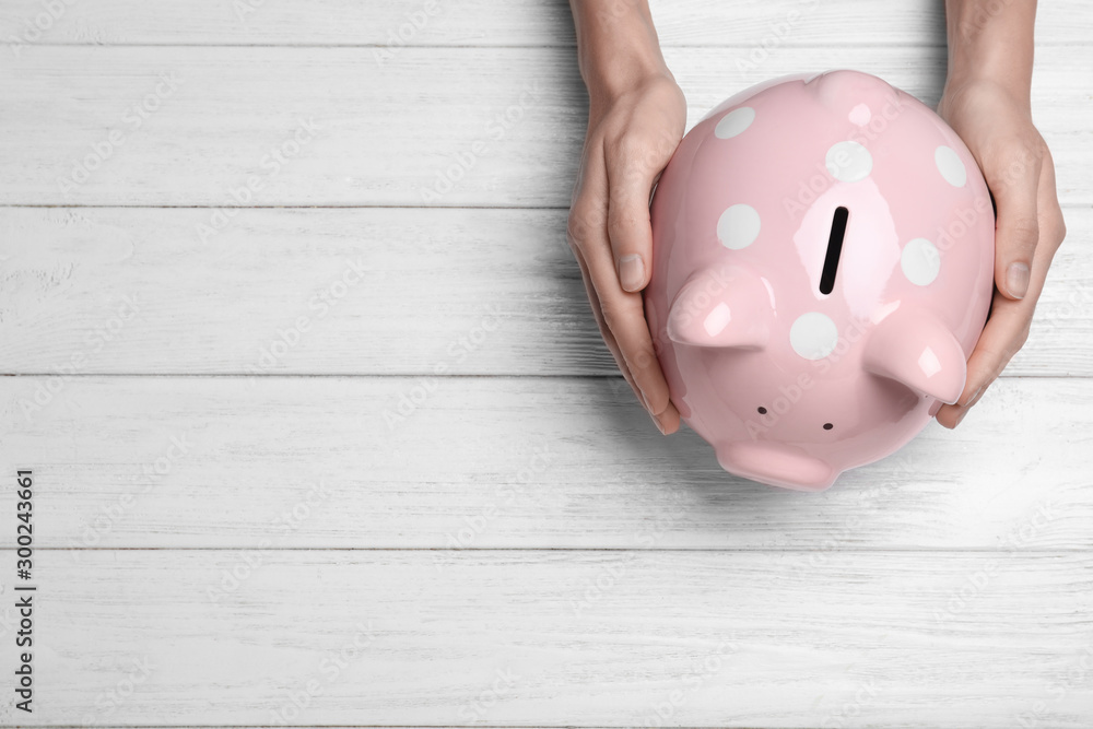 Fototapeta Woman holding piggy bank on white wooden table, top view with space for text. Money savings