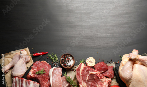 Obraz Flat lay composition with fresh meat on dark table. Space for text - fototapety do salonu