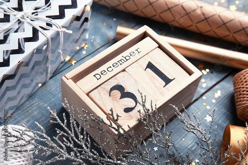 Fotografie, Tablou Wooden block calendar and festive decor on table, closeup