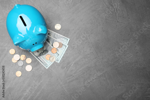 Stampa su Tela Top view of piggy bank and cash on grey stone table, space for text