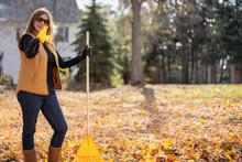 Happy Woman Raking Leaves In Fall