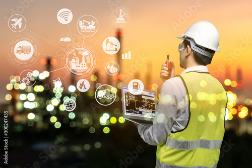 Fototapeta Engineer holding walkie talkie are working order at oil and gas refinery. Industry petrochemical concept image and icon connecting networking using technology. obraz