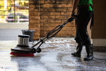 A Man Worker Cleaning The Floor With Polishing Machine