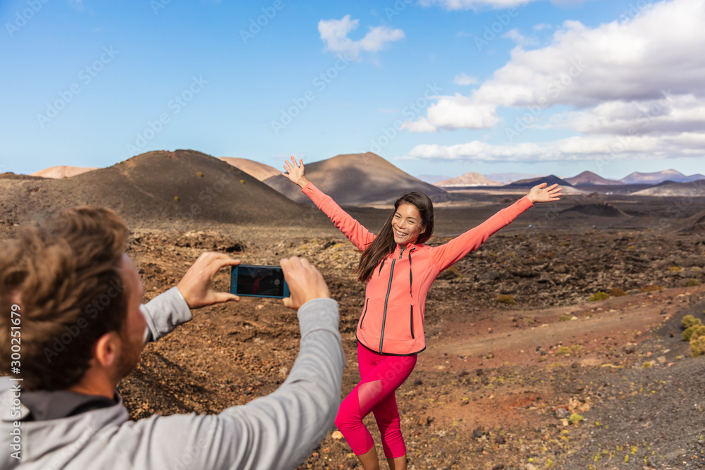 Fototapety, obrazy: Tourists taking picture vlogging outside on Europe travel, girl posing for boyfriend with arms up having fun on Timanfaya National Park, Lanzarote, Canary Islands.