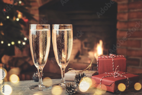Door stickers Alcohol Two glasses with champagne and gifts on a wooden table in a room with a burning fireplace