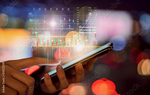 Fotografía Stock exchange market concept, hand trader touching on smartphone with graphs analysis candle line on bokeh colors light in night atmospheric city
