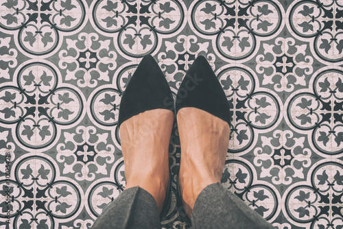 Photo From where I stand first person view perspective of woman standing on tiled floor taking selfie of black suede pointy shoes walking over old fashion ornament pattern tiles in Europe