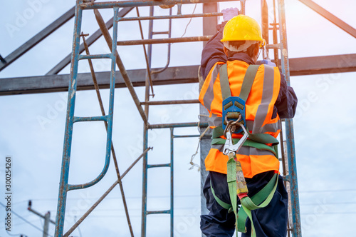 Vászonkép Construction worker wearing safety harness belt during working at high place