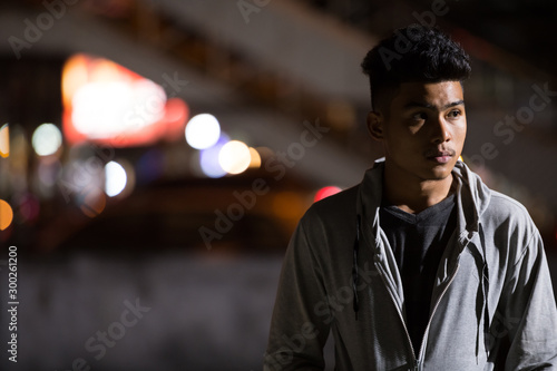 Young Asian man thinking in the city streets at night Canvas Print
