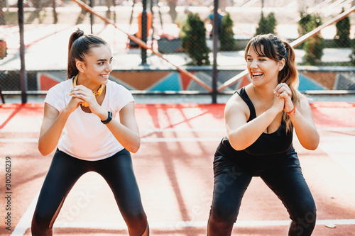 Photo Portrait of a lovely young plus size women laughing while doing exercises for lose weight with her girlfriend in a sport park