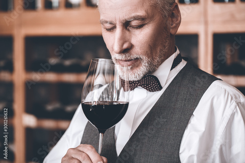 Sommelier Concept. Senior man standing holding glass smelling wine closed eyes joyful close-up - 300261632