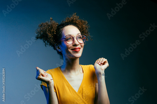 Fototapeta Portrait of a smiling young woman wishing for something, hoping for thew best and looking up in studio obraz