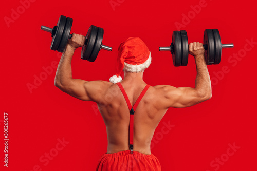 Nude Santa Claus training back with dumbbell Fototapet
