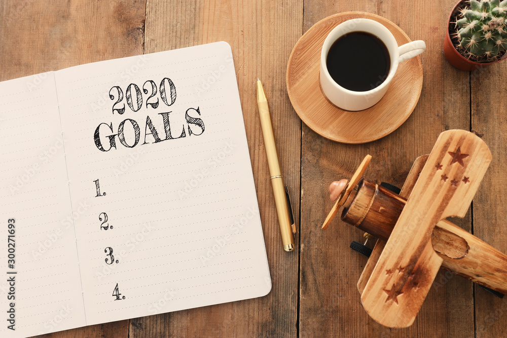 Fototapety, obrazy: Business concept of top view 2020 goals list with notebook, cup of coffee and old plane toy over wooden desk