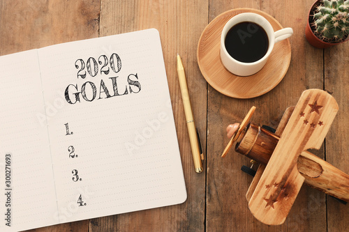 Poster Individuel Business concept of top view 2020 goals list with notebook, cup of coffee and old plane toy over wooden desk