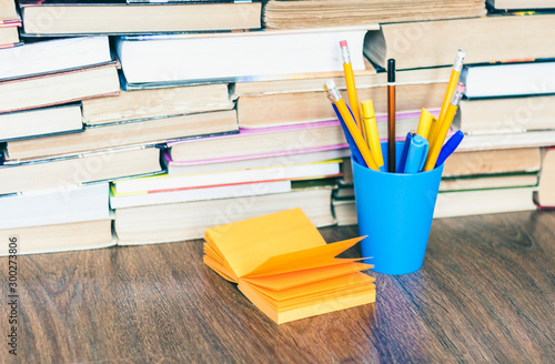 Fotografie, Obraz  Colorful pencils in blue plastic holder and orange note paper, stack of books education back to school background, with copy space for text
