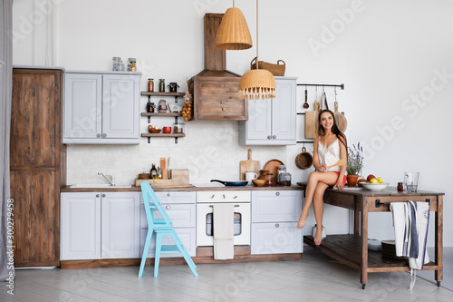 Fotografía  Portrait of a girl sitting on kitchen table by the stove, cooking sauce in pan