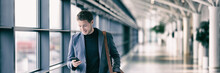 Business Man Texting On Mobile Phone At Airport On Business Trip Using Cellphone Texting Sms Message On Smartphone App - Young Businessman Commuter Lifestyle Panoramic Banner.